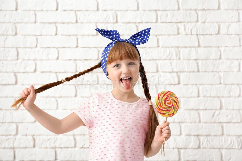 有棒棒糖的逗人喜爱的女孩在白色砖墙附近 免版税库存照片