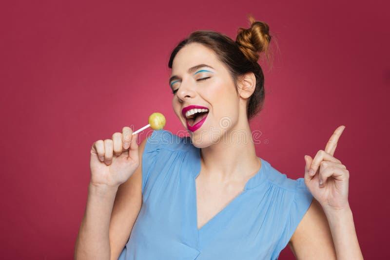 有棒棒糖跳舞和唱歌的愉快的cherming的少妇 库存图片