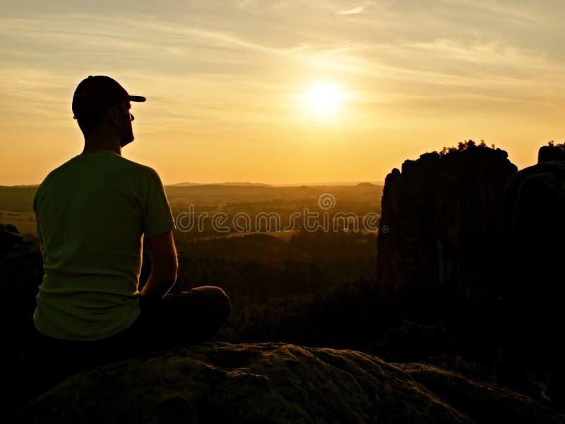 有棒球帽的人在山顶部 岩石剪影  免版税图库摄影