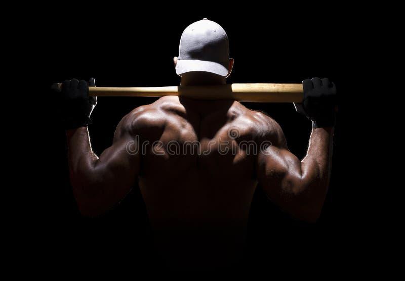 有棒球棒的运动员在肩膀 库存图片