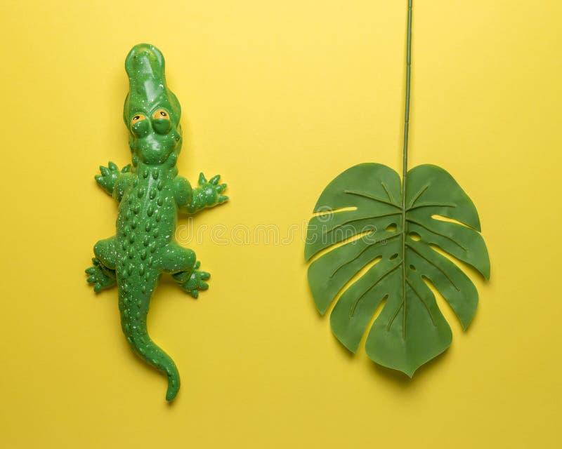 有棕榈叶的绿色鳄鱼玩具在明亮的黄色背景 r 库存图片
