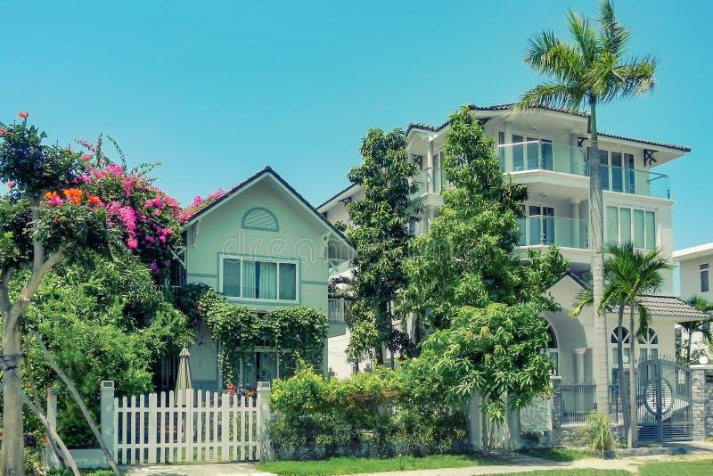有棕榈树、树和风景设计的Ne美丽的三层房子在夏天 免版税库存照片