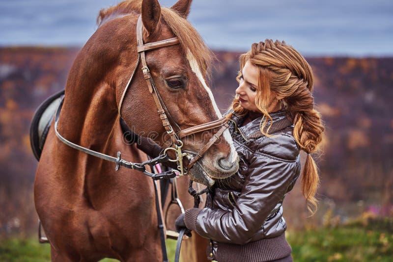 有棕色卷发的一年轻女人爱抚一匹棕色马 马爱抚妇女 库存照片