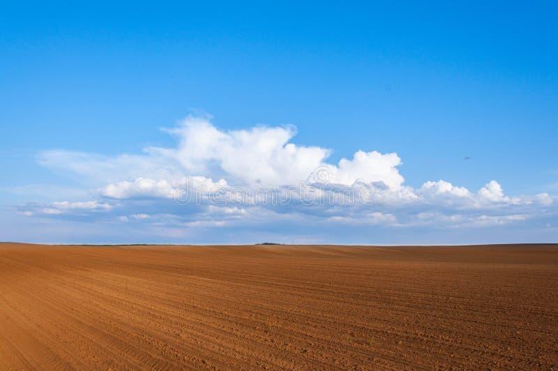 有棕色地面的犁土地和天空蔚蓝和云彩 免版税库存照片