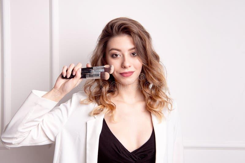 有棕色头发的美丽的少女在她的拿着一把专业构成刷子的手上 库存图片