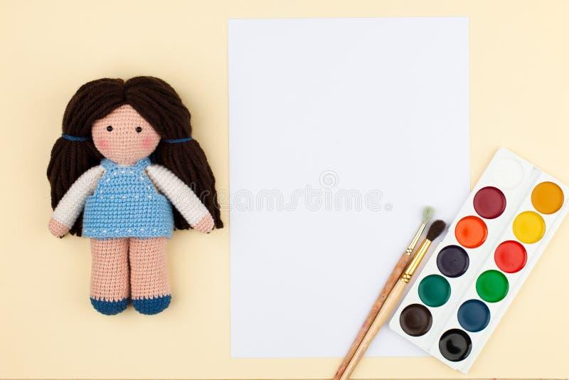 有棕色头发的Amigurumi玩偶、刷子和水彩和空白文本的在软的黄色背景 免版税库存照片