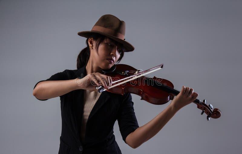 有棕色帽子的夫人在左肩膀上弹小提琴,把小提琴放并且拿着有右手的弓小提琴 免版税图库摄影