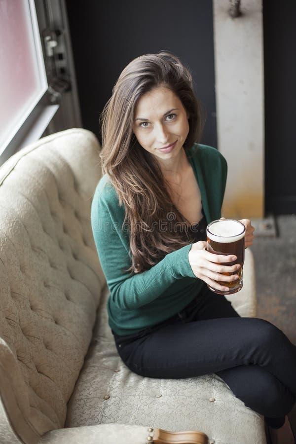 拿着杯子啤酒的美丽的少妇 免版税图库摄影