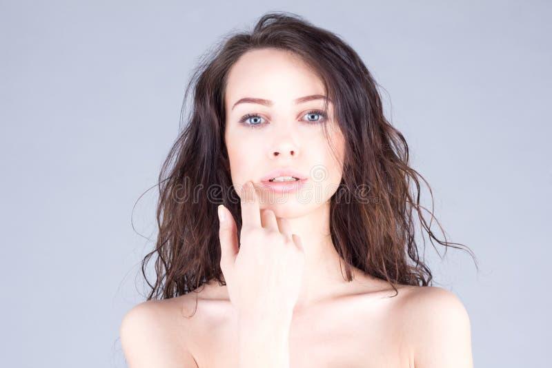 有棕色接触她的面孔的卷发和干净的皮肤的美丽的妇女 库存图片