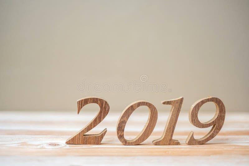有棕色木数字的2019新年快乐在桌和拷贝空间 新的开始、决议、目标和使命 免版税库存照片