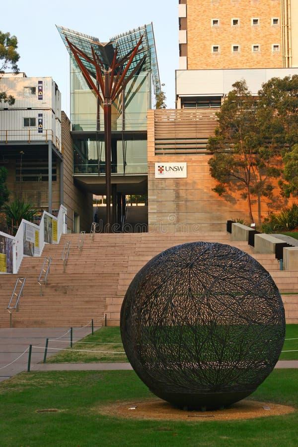 有棕色木材专栏和树枝的现代V形的玻璃机盖在约翰Niland Scientia大厦的台阶在UNSW校园里 免版税图库摄影