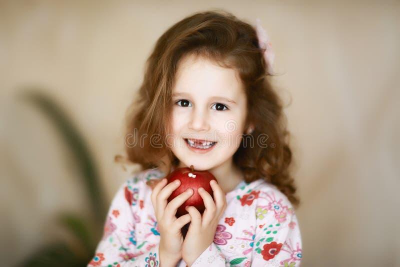 有棕色眼睛的一颗甜矮小的卷曲牙女孩在她的手上微笑并且拿着掉了乳齿的一个红色苹果 库存图片