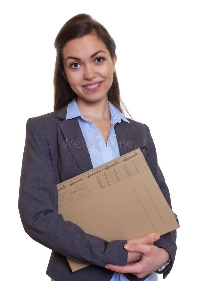 有棕色头发和文件的可爱的女实业家 免版税图库摄影