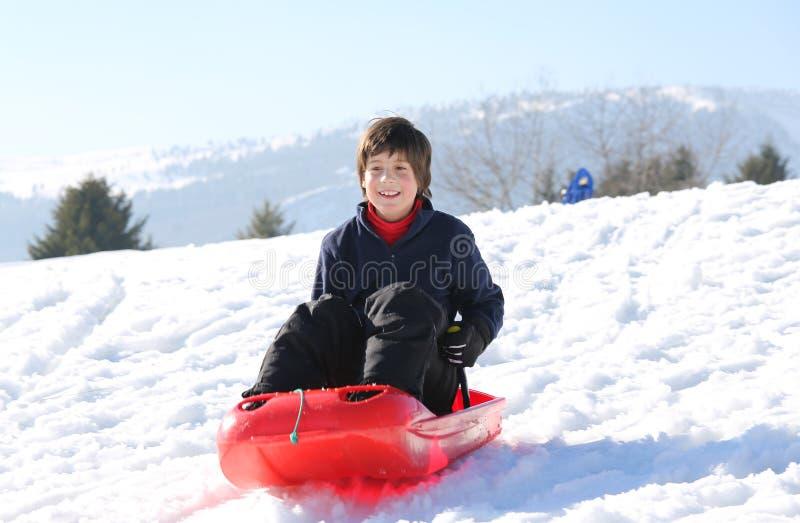 有棕色头发的孩子在冬天使用与在mounta的突然移动 免版税库存图片