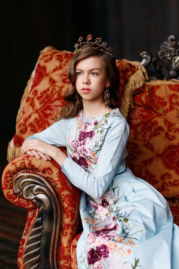 有棕色头发的美丽的棕色目的公主在一件蓝色的礼服 免版税库存图片