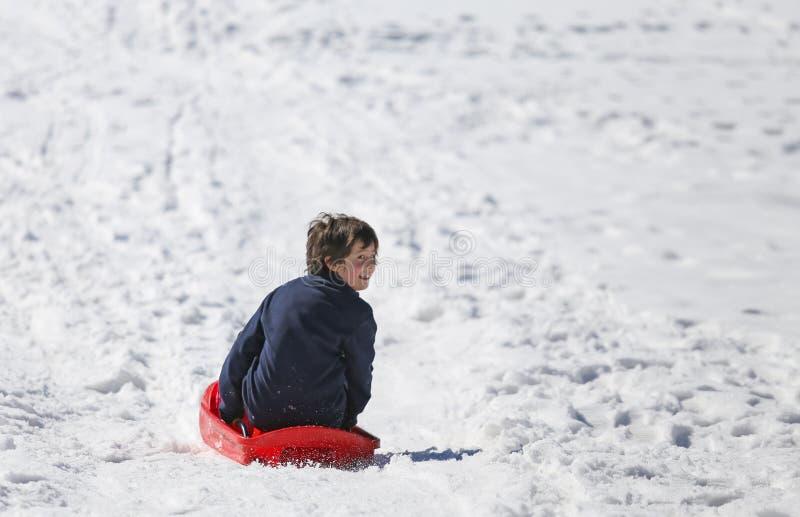 有棕色头发的年轻男孩在冬天使用与突然移动在mo 免版税图库摄影