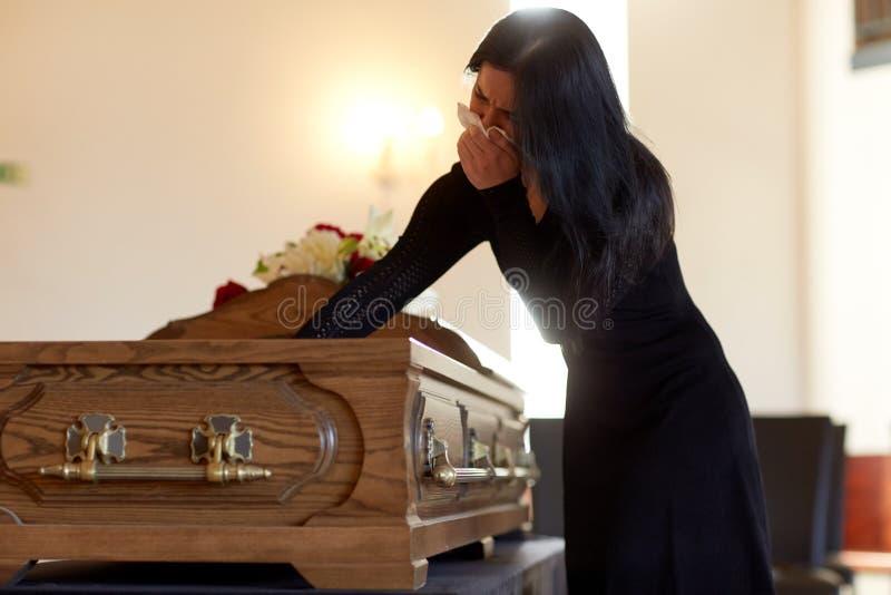 有棺材的妇女哭泣在葬礼的在教会里 免版税库存图片