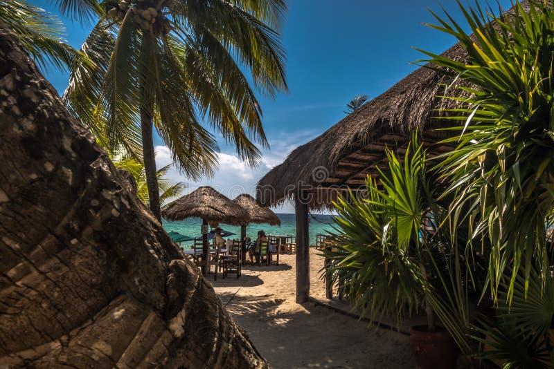 有椅子的传统加勒比墨西哥海滩餐馆和桌、palapa和棕榈树 免版税库存图片