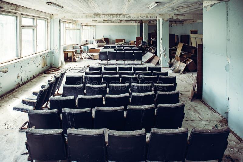 有椅子的观众席室在被放弃的和被破坏的工业工厂,在战争以后的蠕动的年迈的大厦,没有人 库存图片