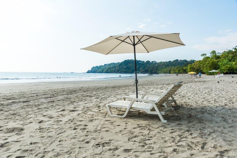 有椅子的遮阳伞在曼努埃尔・安东尼奥公园的Playa埃斯帕迪利亚-哥斯达黎加 库存照片