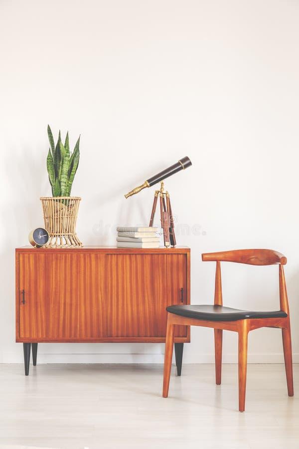 有植物、书、望远镜和时钟的葡萄酒碗柜在白色和明亮的内部的时髦的木椅子旁边与拷贝空间 库存照片