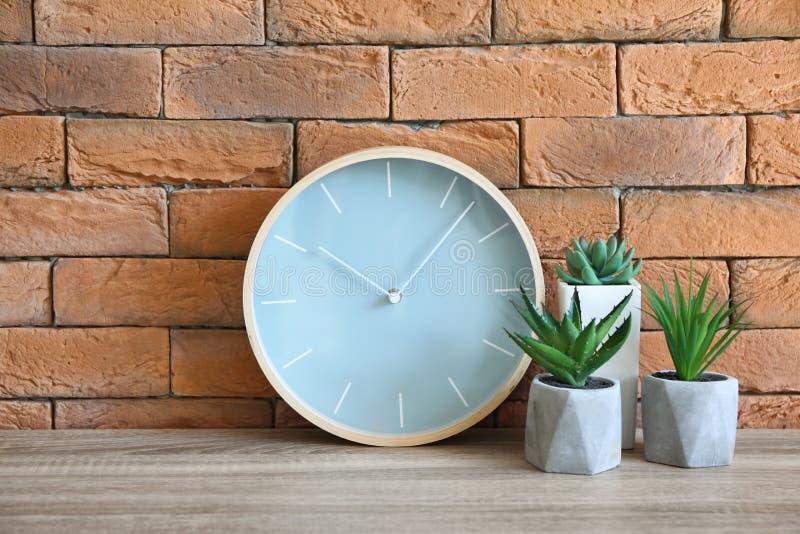 有植物的现代时钟在桌上对砖墙 免版税库存图片
