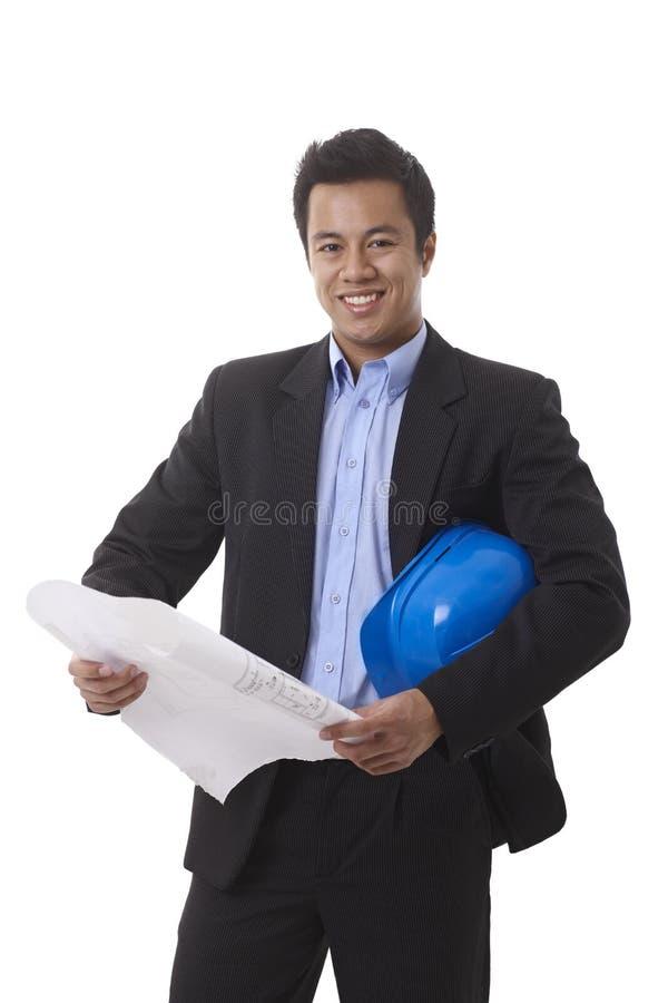 有楼面布置图和安全帽的愉快的建筑师 免版税库存图片