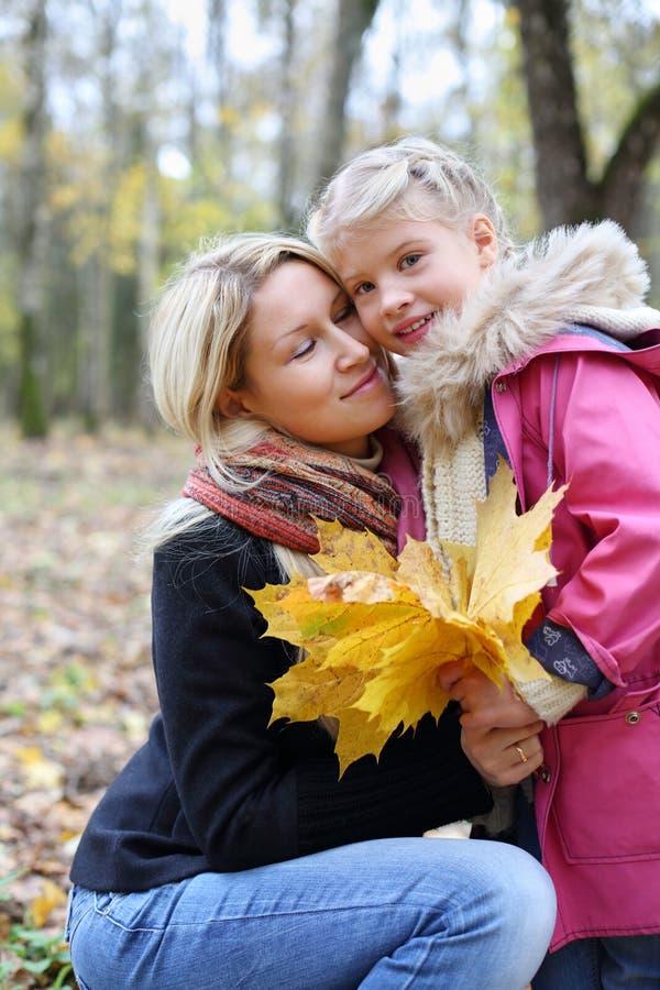 有槭树传单的愉快的母亲拥抱她的女儿 免版税图库摄影