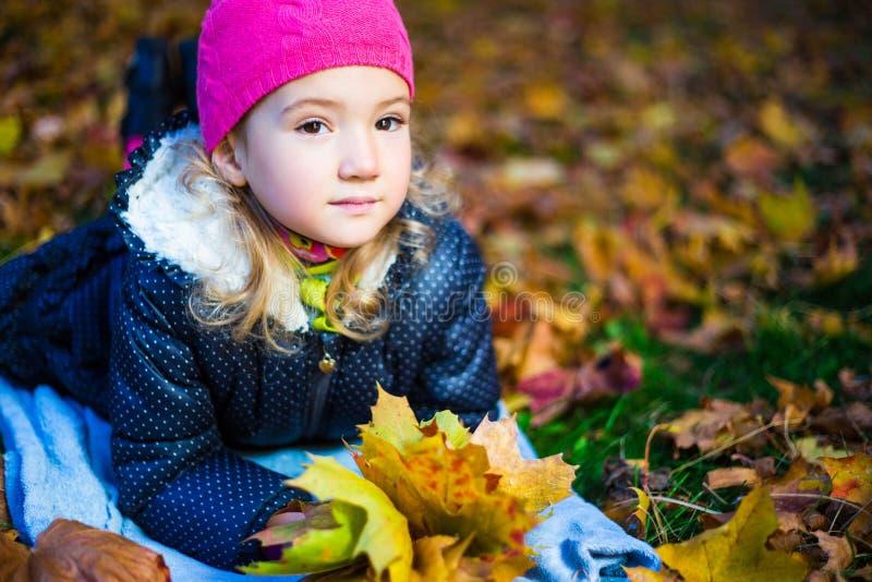 有槭树的作白日梦的美丽的小女孩在aut把说谎留在 免版税库存图片