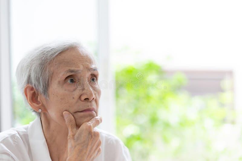 有横渡的在下巴举的胳膊和手的亚裔老年人,认为正面,分析思维搜寻,特写镜头画象  免版税库存图片