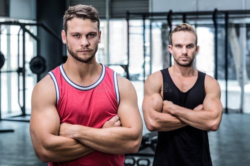 有横渡的胳膊的两个严肃的肌肉人 库存照片