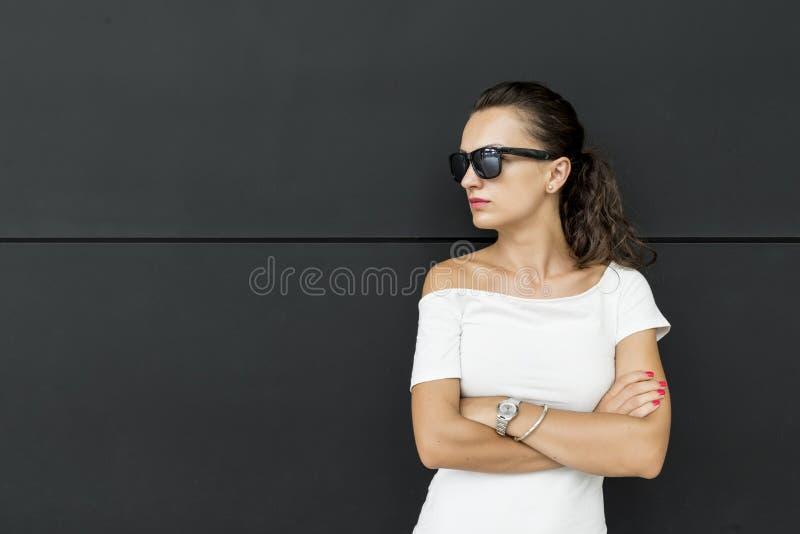 有横渡的胳膊的严肃的年轻深色的妇女 库存图片