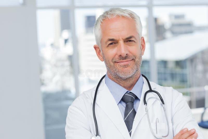 有横渡的胳膊的严肃的医生 库存照片
