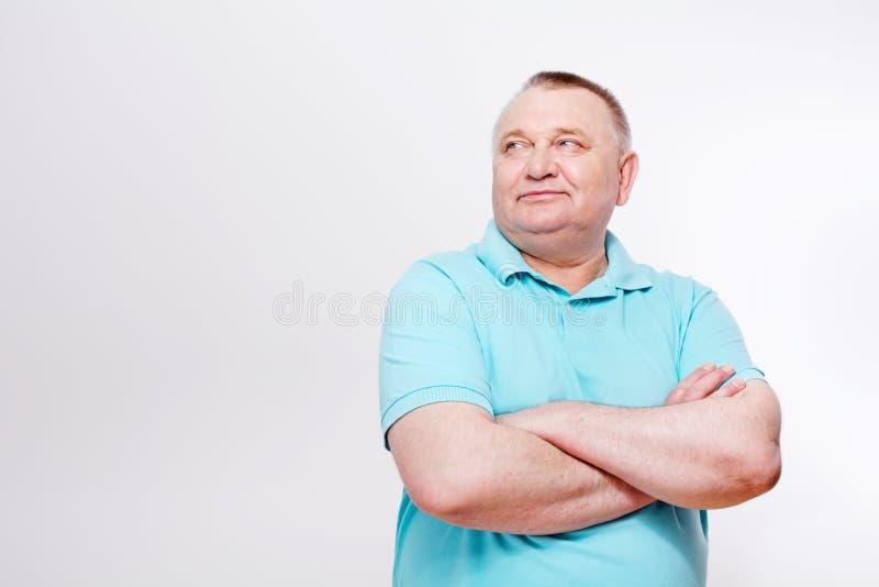 有横渡的胳膊的老人在白色 库存照片