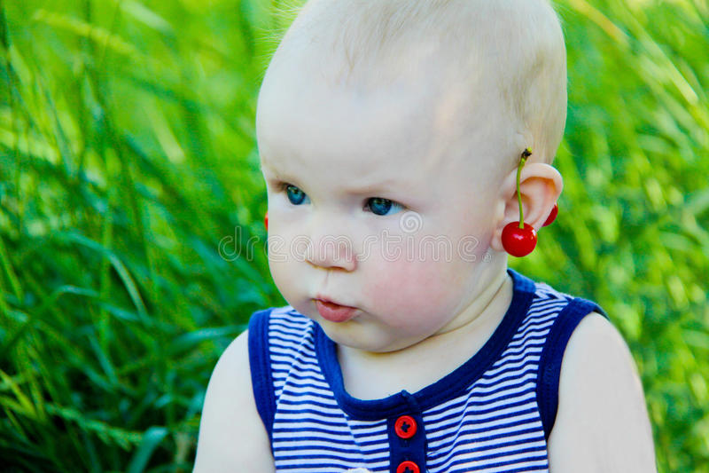 有樱桃耳环的女婴 免版税库存照片