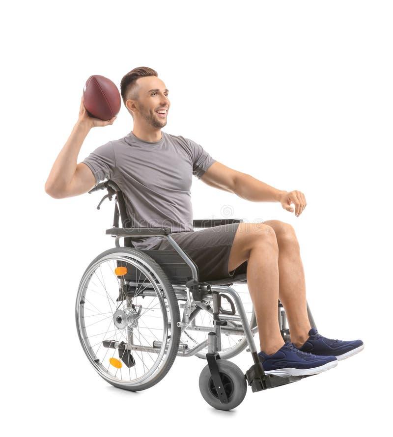 有橄榄球球的年轻人在轮椅坐白色背景 免版税库存照片