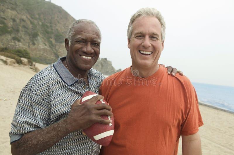 有橄榄球的两个人在海滩(画象) 库存图片