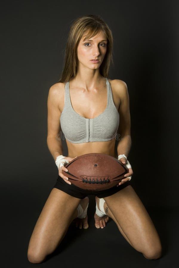 有橄榄球的女性运动员 免版税图库摄影