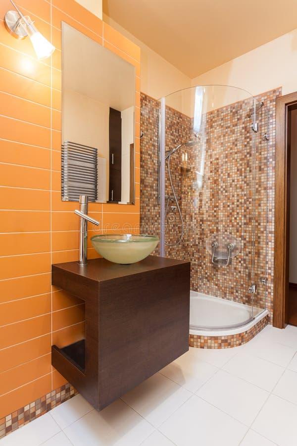 优等的家的橙色卫生间 免版税库存图片