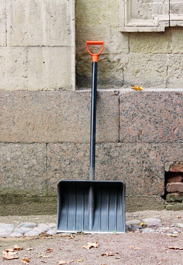 有橙色把柄的新的黑铁锹倾斜对宫殿等待的清除的墙壁从胡同下落的叶子的 免版税库存图片