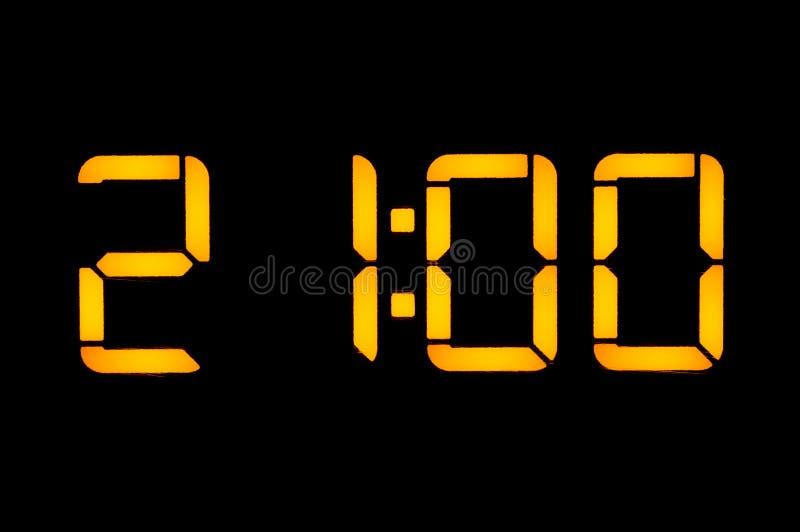 有橙色数字的电子数字钟在黑背景在晚上显示时间二十一零的零的时 库存照片