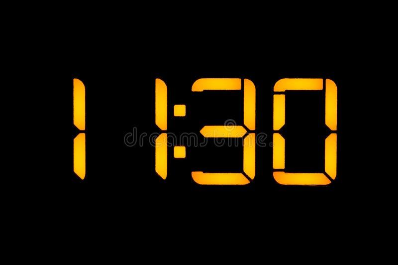 有橙色数字的电子数字钟在黑背景早晨显示十一三十时的时期 Isolat 免版税库存照片