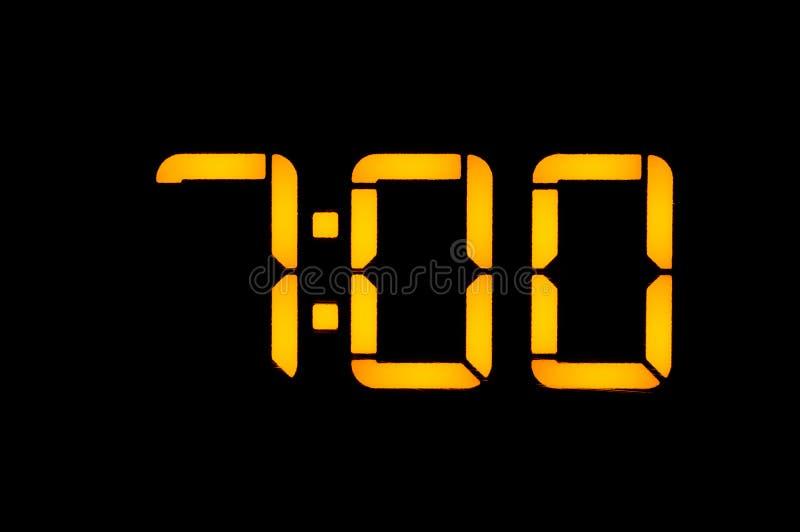 有橙色数字的电子数字钟在黑背景早晨显示时间七零时 孤立,关闭 免版税库存照片