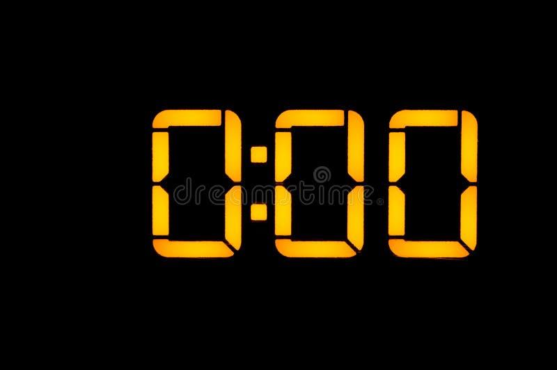 有橙色数字的电子数字钟在黑背景早晨显示时间十二零零或二十四 库存图片