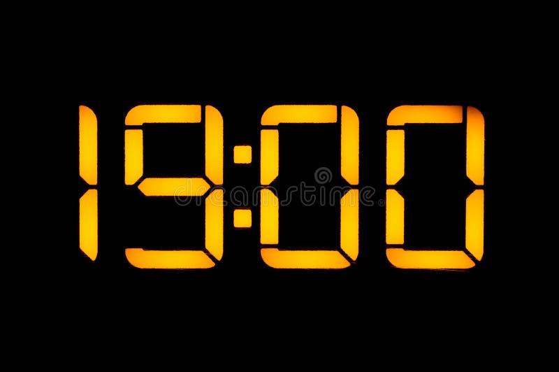 有橙色数字的电子数字钟在黑背景显示时间十九零在晚上调零 孤立, 库存照片