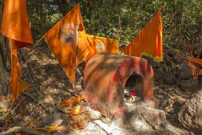 有橙色旗子的红色印度寺庙在绿色森林里 免版税库存图片