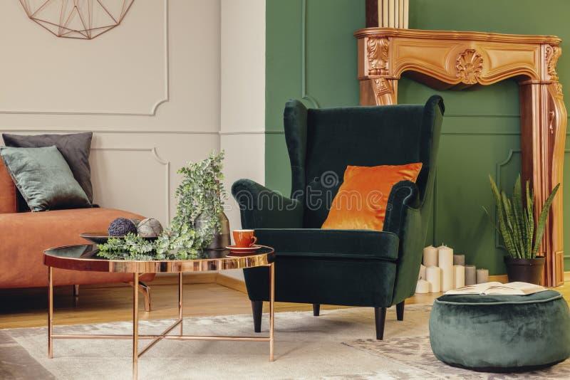 有橙色枕头的舒适的鲜绿色扶手椅子 免版税库存照片