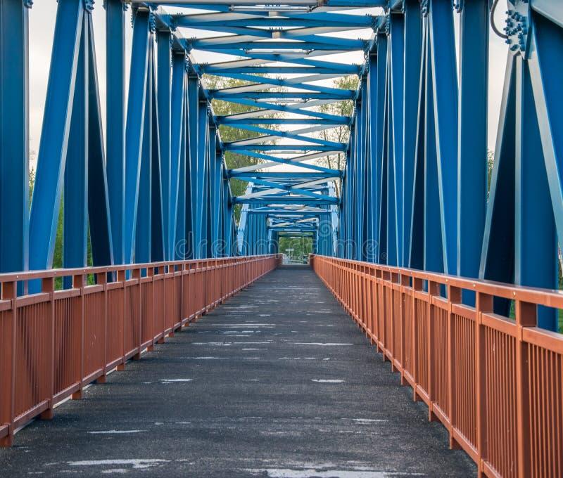 有橙色栏杆和木涂上的特写镜头的金属蓝色步行桥建筑 免版税库存照片