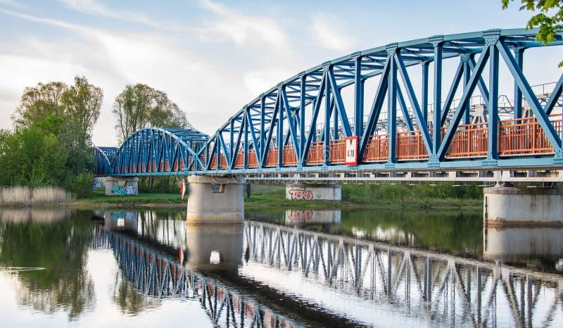 有橙色栏杆的蓝色步行桥在河美妙地被反射 免版税图库摄影