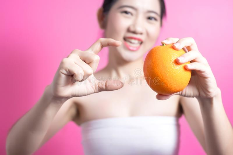 有橙色概念的亚裔妇女 微笑和拿着桔子的她 秀丽面孔和自然构成 隔绝在桃红色背景 库存照片